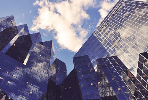 Upward perspective view of tall glass office buildlings